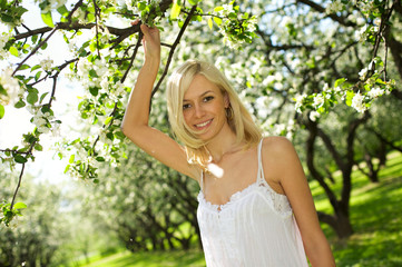 Young beautiful smiling woman in blooming gardens