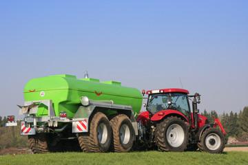 Roter Traktor mit grünem Fasswagen