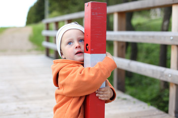 Little boy hugging post