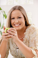 Happy woman holding tea cup