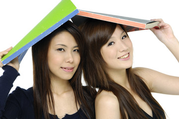 Pretty asian smiling and holding book on head
