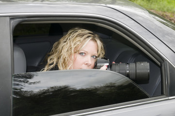 undercover secret agent woman spying with camera in dark car