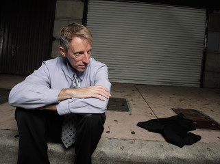 Un employed businessman on the curb