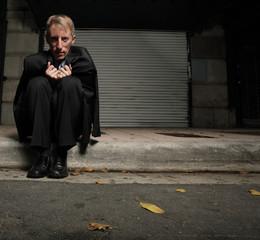 Unemployed businessman sitting on the street