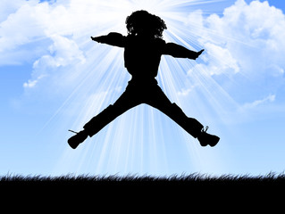 Child jumping against bright sun