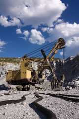 an excavator in opencast mine under skies