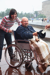 man in an invalid carriage and his wife on walk