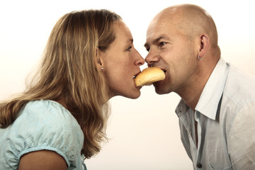 Man and woman eating a roll