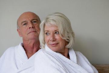 Portrait d'un couple de seniors souriants en peignoir