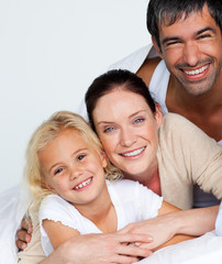 Parents and daughter on bed smiling at the camera
