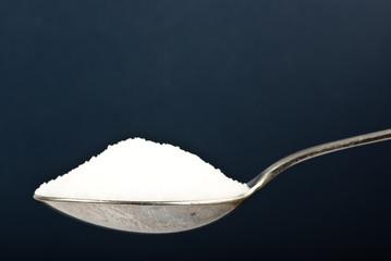 sugar on spoon blue background