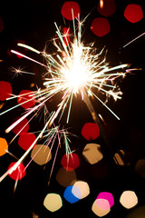Holiday sparkler on blurred Christmas light background