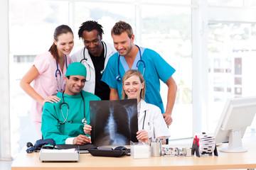Nurse, doctors and surgeon examining an X-ray