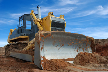 Close-up view of heavy bulldozer standing in sandpit