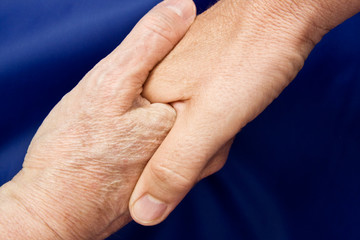 Close up of a hand shake against a blue background