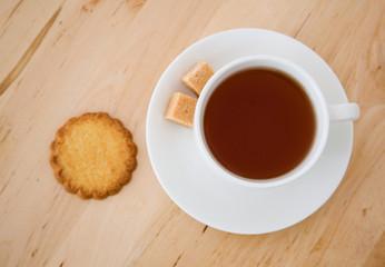 Cup of black tea, sugar and biscuits