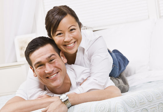 Happy Couple Posing on a Bed