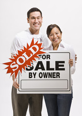 Attractive couple with sold sign