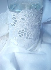 glass with water is turned in white fabric with a lace