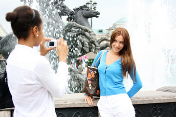 Two girls tourists are photographed in Moscow (Russia)