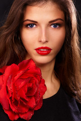 young beautiful brunettes with red lips decorated with rose
