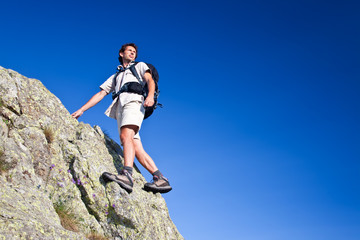 Young man standing on a rock over a deep blue sky