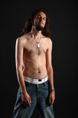 Rebel with long hair and topless slim body isolated on black