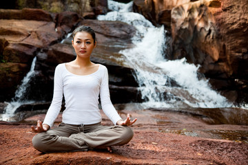 Woman doing zen exercise near a waterfall