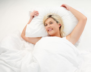 Happy young woman relaxing in bed