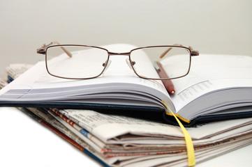 Pile of newspaper with eyeglasses