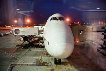 Flugzeug am Gate bei Nacht von aussen wird beladen