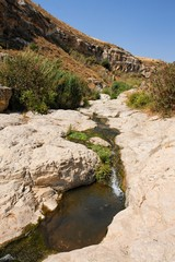 Narrow stream flows in stone banks on Golan Heights, Israel