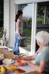 Femme senior observant une jeune femme nettoyant les vitres