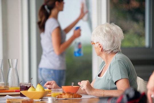 Femme agée prenant son petit déjeuner observant une femme