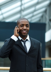 Ethnic businessman on phone and smiling at the camera