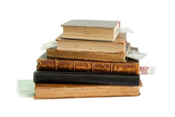 Stack of old books with banknote bookmarks isolated