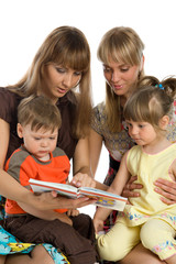 Two mothers read books to their children