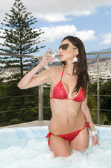 sexy woman having a drink in outdoor jacuzzi
