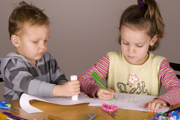 Boy and girl doing arts and craft with pen, scissors and glue