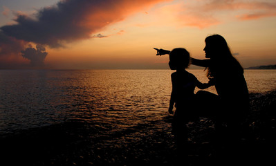 Silhouettes of the woman and child beside seaside on sundown
