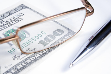 eye-glasses, pen and banknote