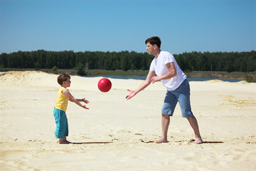 father and son throw each other ball on sand Wall mural
