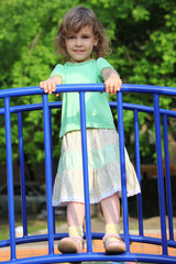 little girl stands on bridge on playground