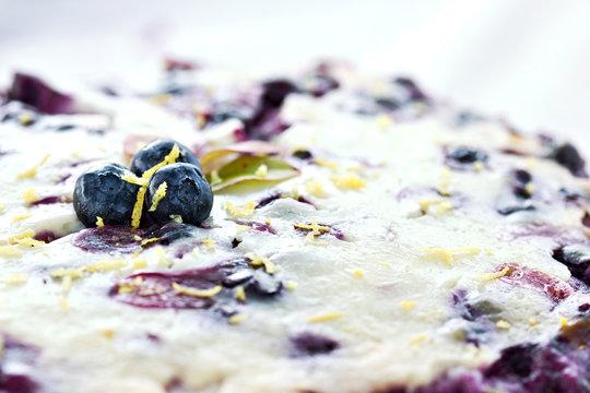 Macro of blueberry flan with lemon zest.