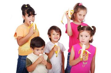 Group of children eating banana isolated