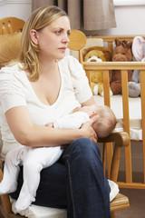 Worried Mother Breastfeeding Baby In Nursery