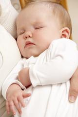 Mother Holding Sleeping Baby In Nursery