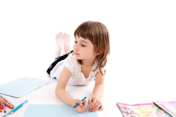 Little girl draws a picture.