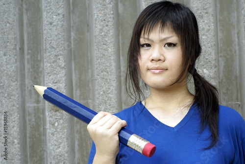 Young Asian Teen Girl In Blue Holding Large Pencil