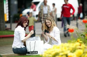 zwei Freundinnen  beim Shoppen in der Stadt , zählen ihr Geld
